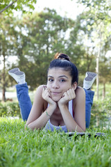 Jolly beautiful teenage girl sitting on grass.