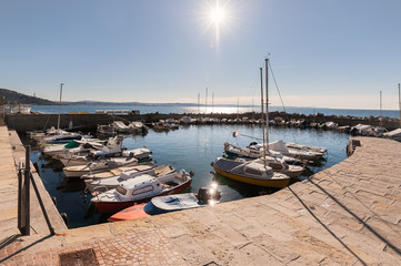 Pleasure boats moored in small harbor in sunny day.