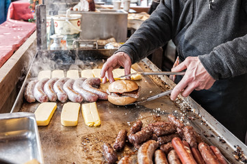 Hands of the cook preparing a sandwich with sausage.