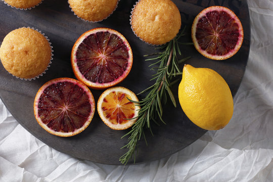 Close up of cupcake with rosemary and citrus fruits on cutting board