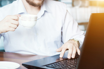 Caucasian businessman working in office on laptop and drink coffee or tea. Business and office corporate working concept.