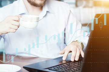 Finance advisor business man working on tablet in office and drink coffee or tea. VR graphs and charts on hologramm shows growing in economy