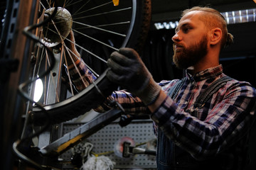 Handsome stylish male wearing a flannel shirt and jeans coverall, working with a bicycle wheel in a repair shop.