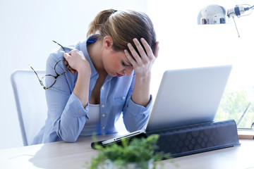 Tired young woman with headache using her laptop at home.