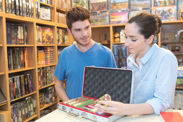 young man buying poker chip in a game store