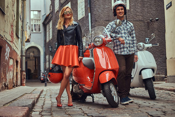 Attractive couple, a handsome man and sexy female standing on an old street with two retro scooters.