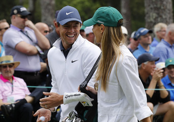 Rory McIlroy of Ireland talks with his wife Erica during the par 3 contest at the 2018 Masters golf tournament in Augusta