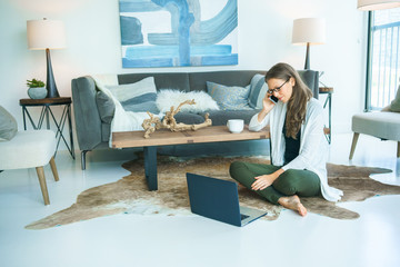 Young woman sitting on floor using laptop and talking on mobile phone