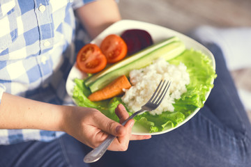 A girl holds a plate with rice and vegetables. Healthy eating concept. Girl in jeans and a plaid shirt. Proper nutrition. Diet. Health. Vegetarian food. Vegans food. Small depth of field. Toned image.