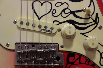 """The bridge, the volume and the tune bottom are seen on the body of an electric guitar as it is displayed for sale inside the vintage guitars shop """"Headbanger"""" in Madrid"""