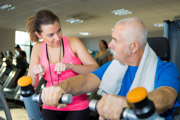 female fitness coach advising senior man on bicycle