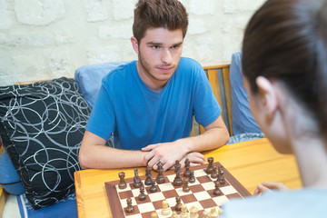 Serious young couple playing chess