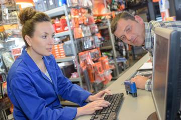 Customer watching sales clerk on computer