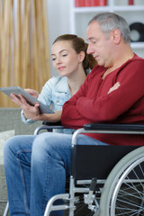 young woman teaching the man on the wheelchair with technology
