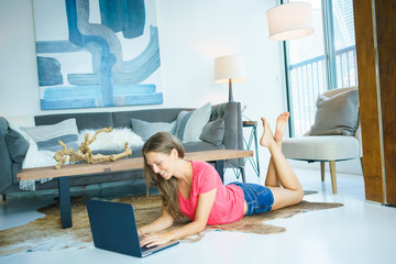 Happy young woman using laptop while lying on floor at home