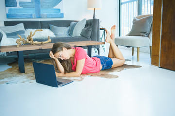 Sad young woman using laptop while lying on floor at home