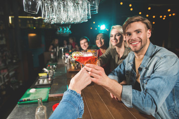 Close-up lady arm holding appetizing alcohol beverage. She chinking glasses with beaming friends. Happy women and males relaxing in bar concept