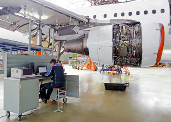 Aircraft service, diagnostics, inspection, repair, view of the engine of the aircraft and with a technician at the computer in the air industry hangar.