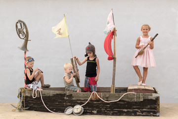 Happy boys in costume pirates and beautiful girl play on toy sailboat built from an old boat. Funny company have good time together