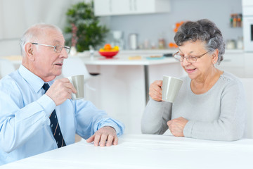 Photo sur Aluminium Pharmacie happy senior couple sitting at the table and drinking coffee