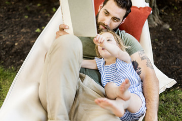 High angle view of daughter with father reading book while lying on hammock at yard