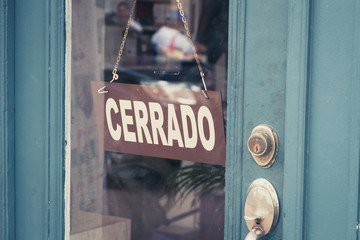 "Cerrado (closed) sign on door - spanish word ""cerrado"" (closed) on shop entrance -"