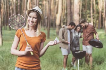 Satisfied woman standing in forest and holding racket and shuttlecock. Her friends making grilled food on background