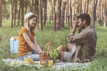 Cheese. Concentrated man taking photo of his girlfriend during picnic. Woman is sitting and smiling