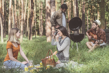Carefree youth relaxing in forest. Glad women photographing each other. Calm men cooking food on grill and playing the guitar
