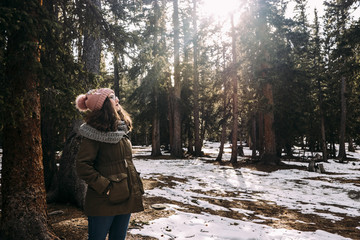 Woman wearing warm clothing while standing at forest during winter