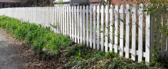 Perspective view of white picket fence.