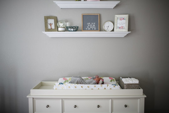 Newborn baby girl lying on changing table