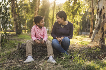 Mother and son talking while sitting in forest