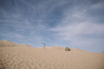 Mid distance view of boy against cloudy sky at desert during sunny day