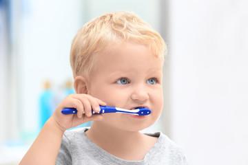 Cute little child cleaning teeth in bathroom