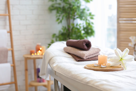 Towels, candles and flower on massage table in spa salon