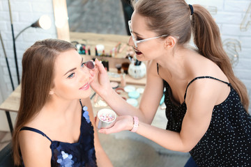 Professional makeup artist working with beautiful young woman in studio