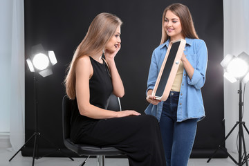 Professional makeup artist working with beautiful young woman in photo studio