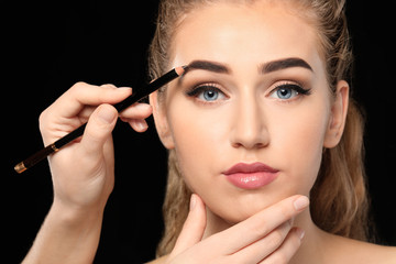 Young woman undergoing eyebrow correction procedure on dark background
