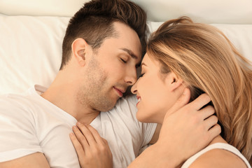 Beautiful young couple sleeping in bed at home