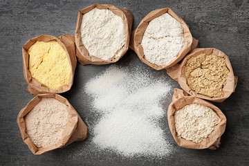 Paper bags with different types of flour on gray background