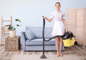 Young woman hoovering carpet with vacuum cleaner in living room