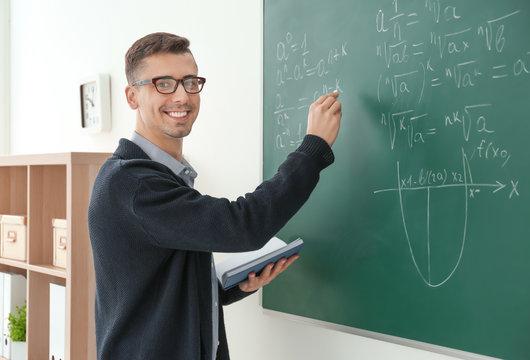 Young male teacher writing on blackboard in classroom