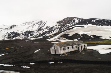 Abandoned house on landscape while snowcapped mountain in background