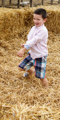 Boy playing on hay