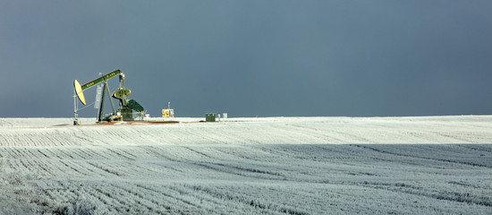 Panoramic view of pumpjack at oil industry on field against sky during winter