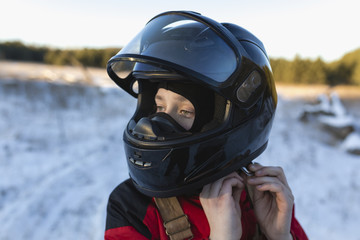 Close-up of teenage boy wearing helmet on snow covered field against sky
