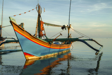 Balinese Fishing Boats Anchored in the Village of Pemuteran. Balinese fishing boats, called jukung, in the bay of northwest Bali, Indonesia during a beautiful sunrise.