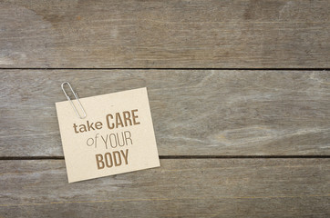 Take care of your body, wooden background with brown paper sheets or note.