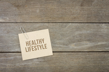 Healthy lifestyle conceptual, wooden background with brown paper sheets or note.